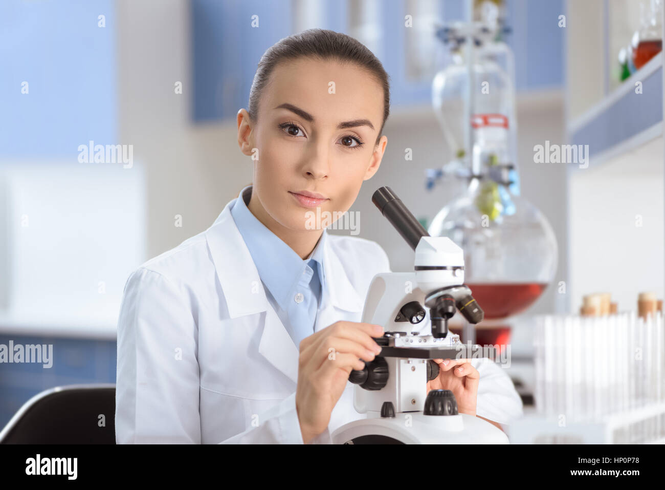 scientist in lab coat working with microscope and looking at camera - Stock Image