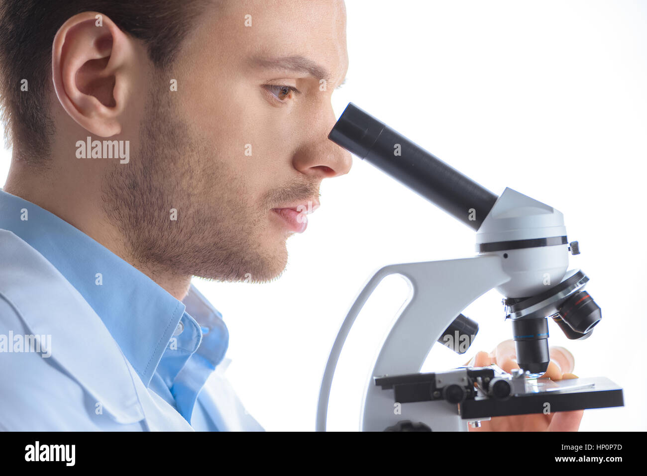 man scientist looking through microscope on white Stock Photo