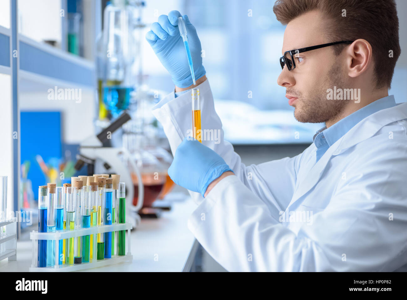 chemist making experiment in laboratory - Stock Image