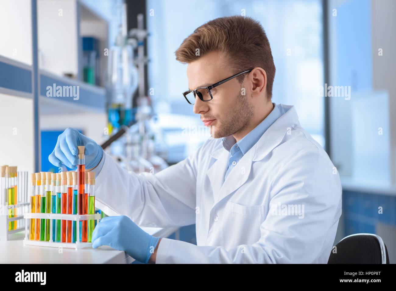 scientist in eyeglasses working with test tubes in lab - Stock Image