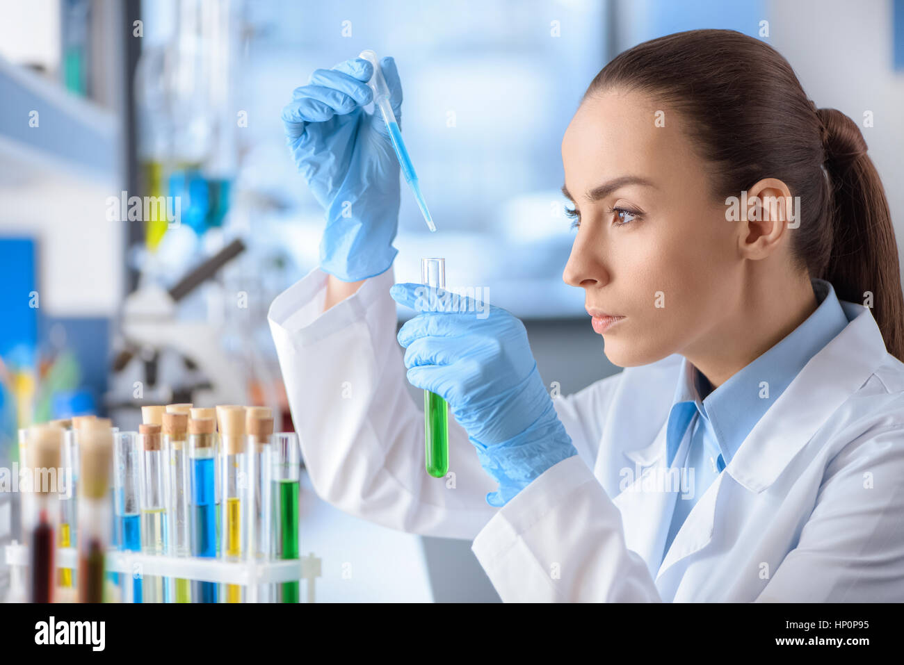 concentrated scientist working with laboratory tube - Stock Image