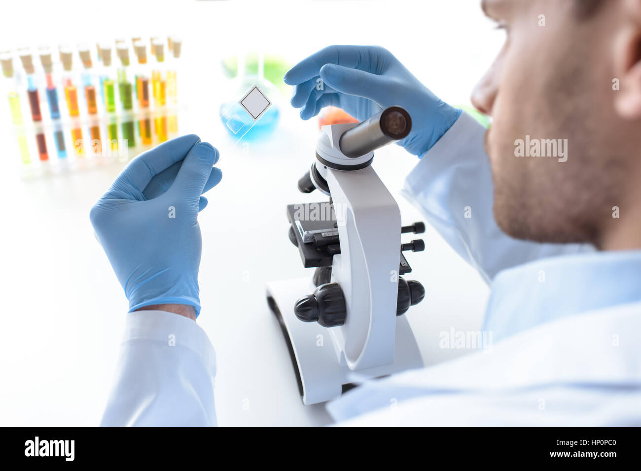 scientist working with microscope in laboratory - Stock Image