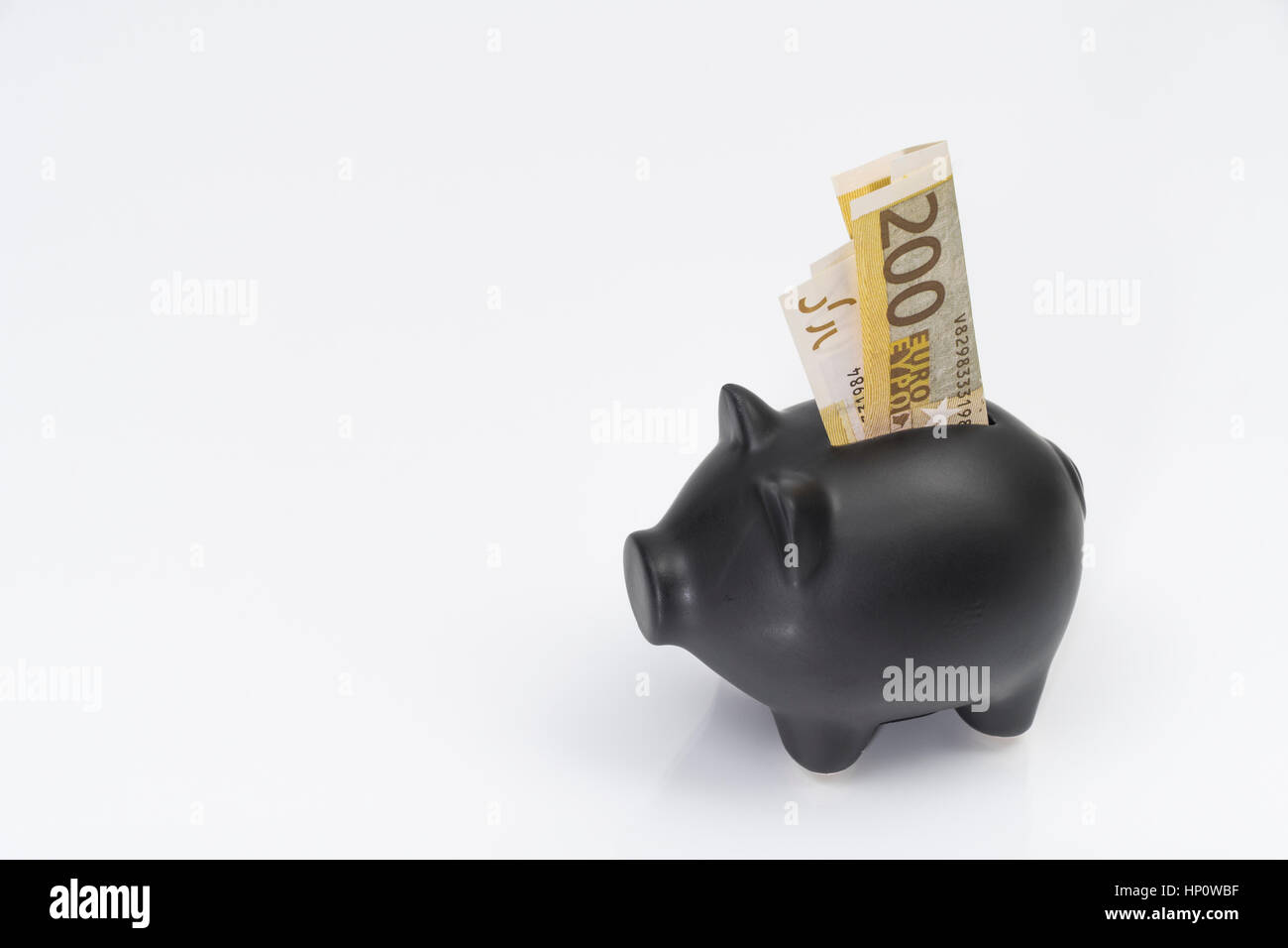 Black Piggy bank with 200 Euro banknote placed in coin slot. Metaphor for personal savings, or EU / European / Brussels Stock Photo