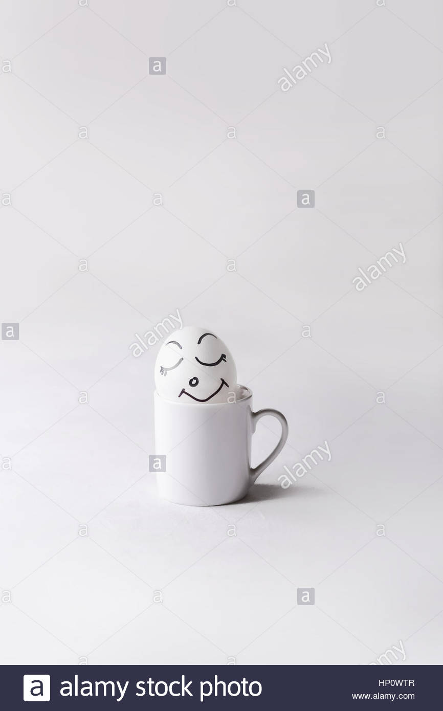 Chicken egg with a pretty funny face in a small white cup