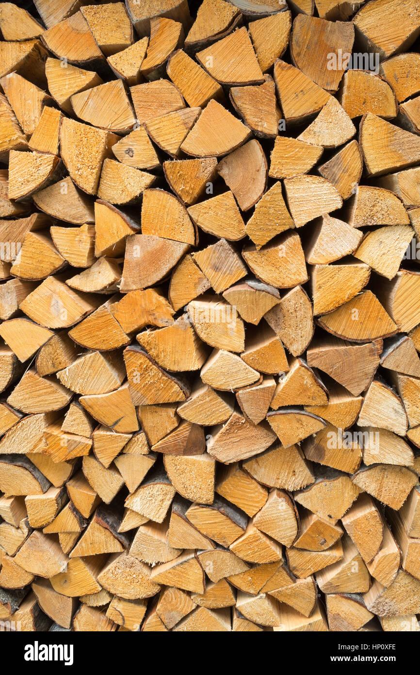 firewood - seasoned kiln-dried split logs neatly stacked background - Stock Image