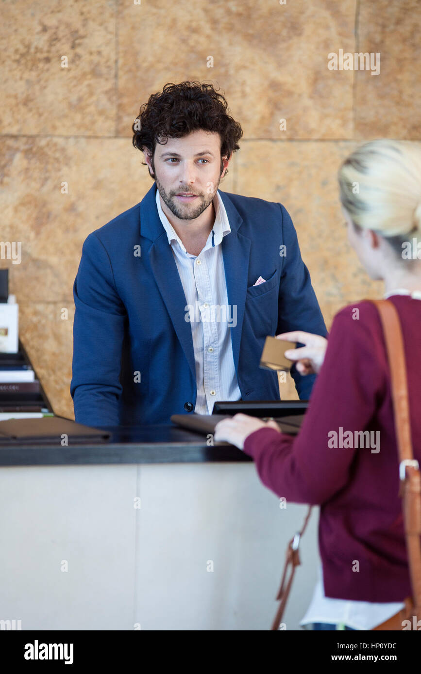 Hotel receptionist assisting guest - Stock Image