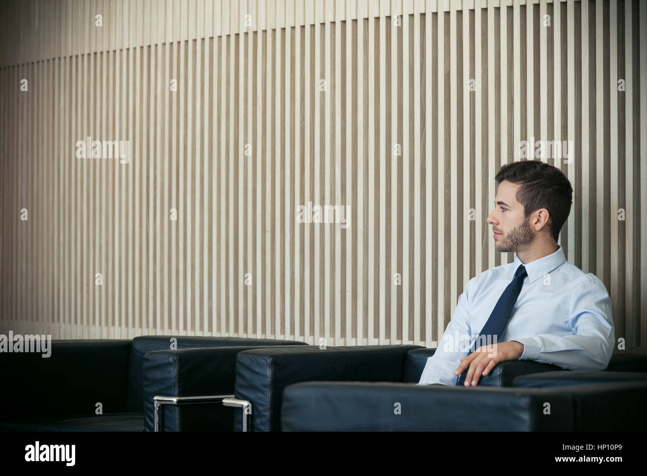 Businessman sitting in waiting room - Stock Image