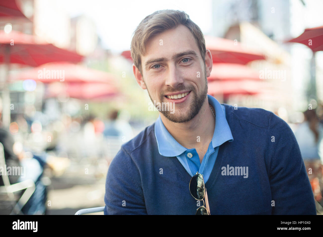 Young man smiling outdoors, portrait - Stock Image