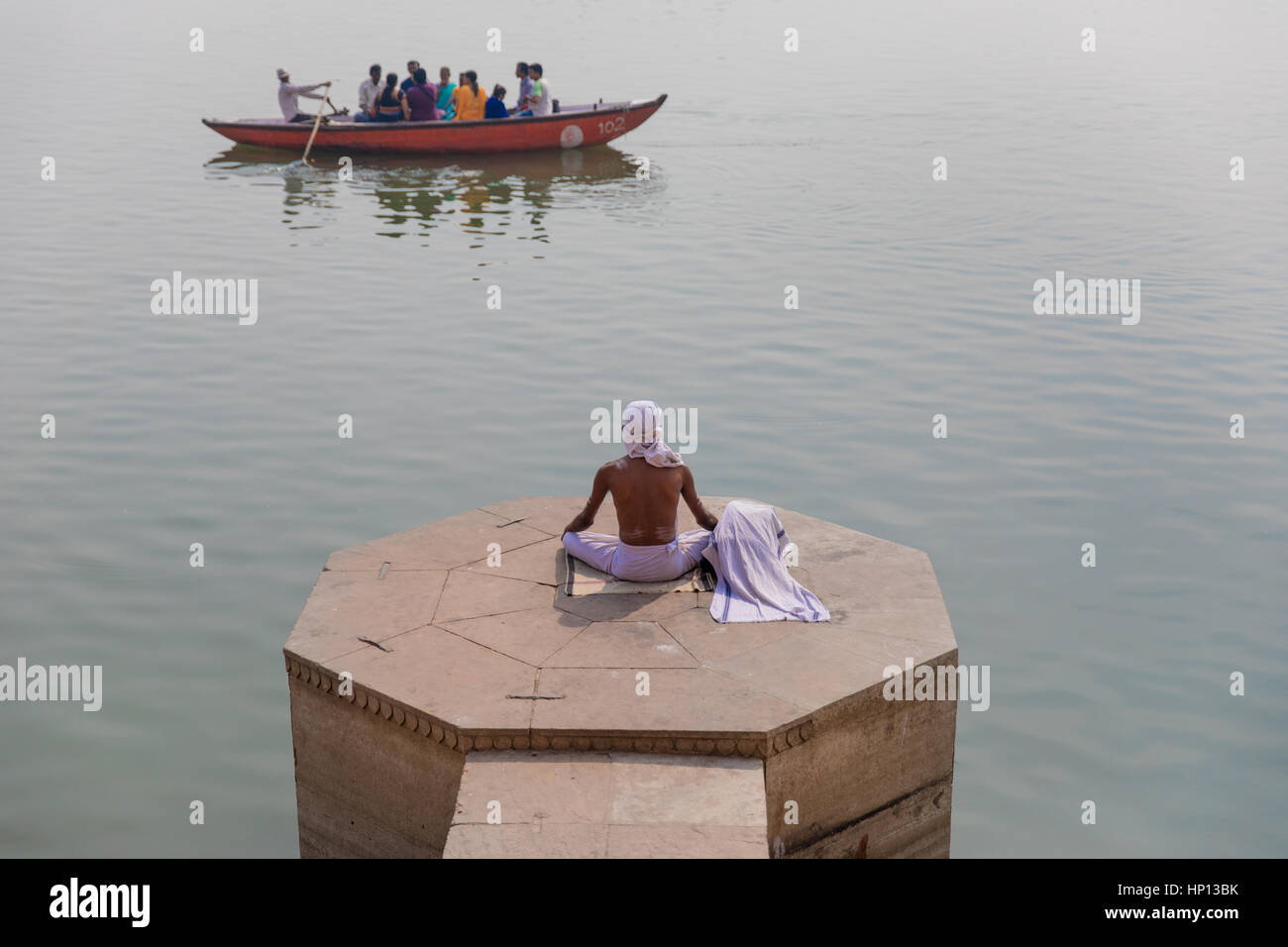 A man meditates on the Ganges River in Varanasi, one of India's holiest cities. Varanasi is a popular destination - Stock Image