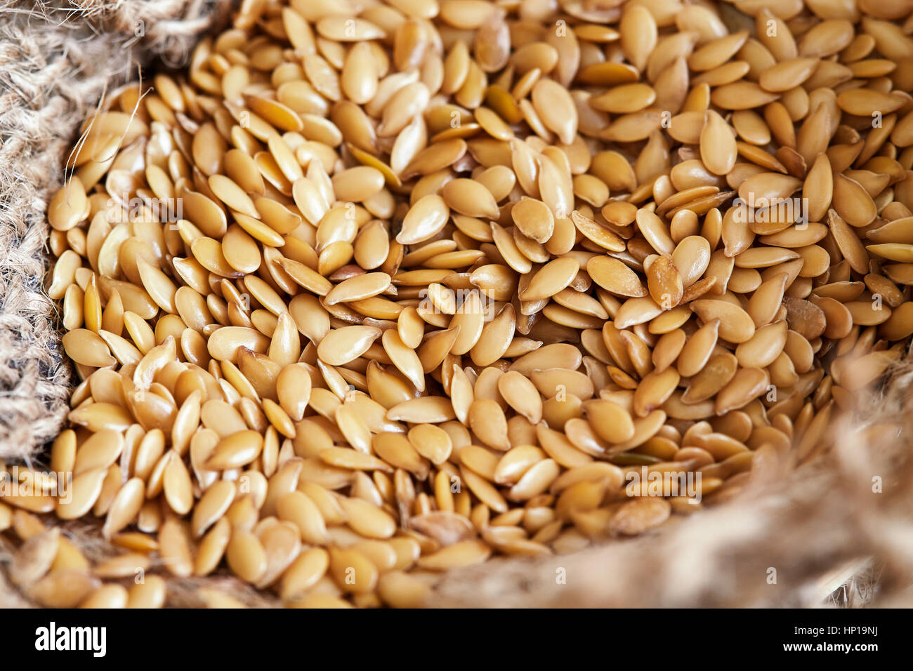 Close-up of golden sesame seeds in burlap bag - Stock Image