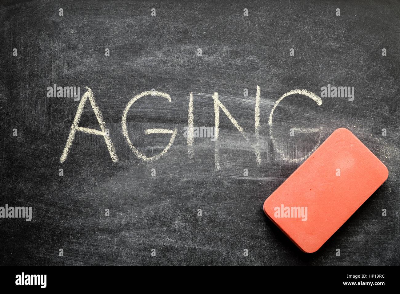 erasing aging, hand written word on blackboard being erased concept - Stock Image