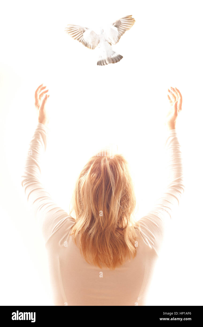 blond woman with open arms and a pigeon flying away - Stock Image