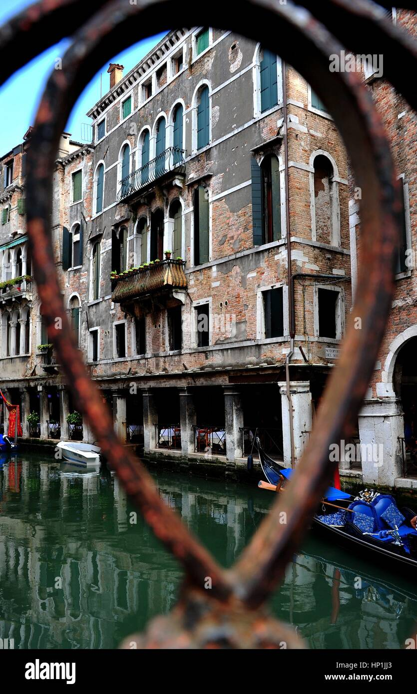 A historic building in the San Marco district of Venice (Italy), photographed by the cast-iron railings of a bridge, - Stock Image