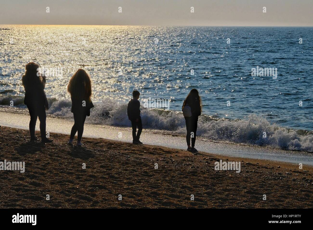 West Bay, Dorset, UK. 18 February 2017. A group of young people are silhouetted by the morning sun as half term Stock Photo