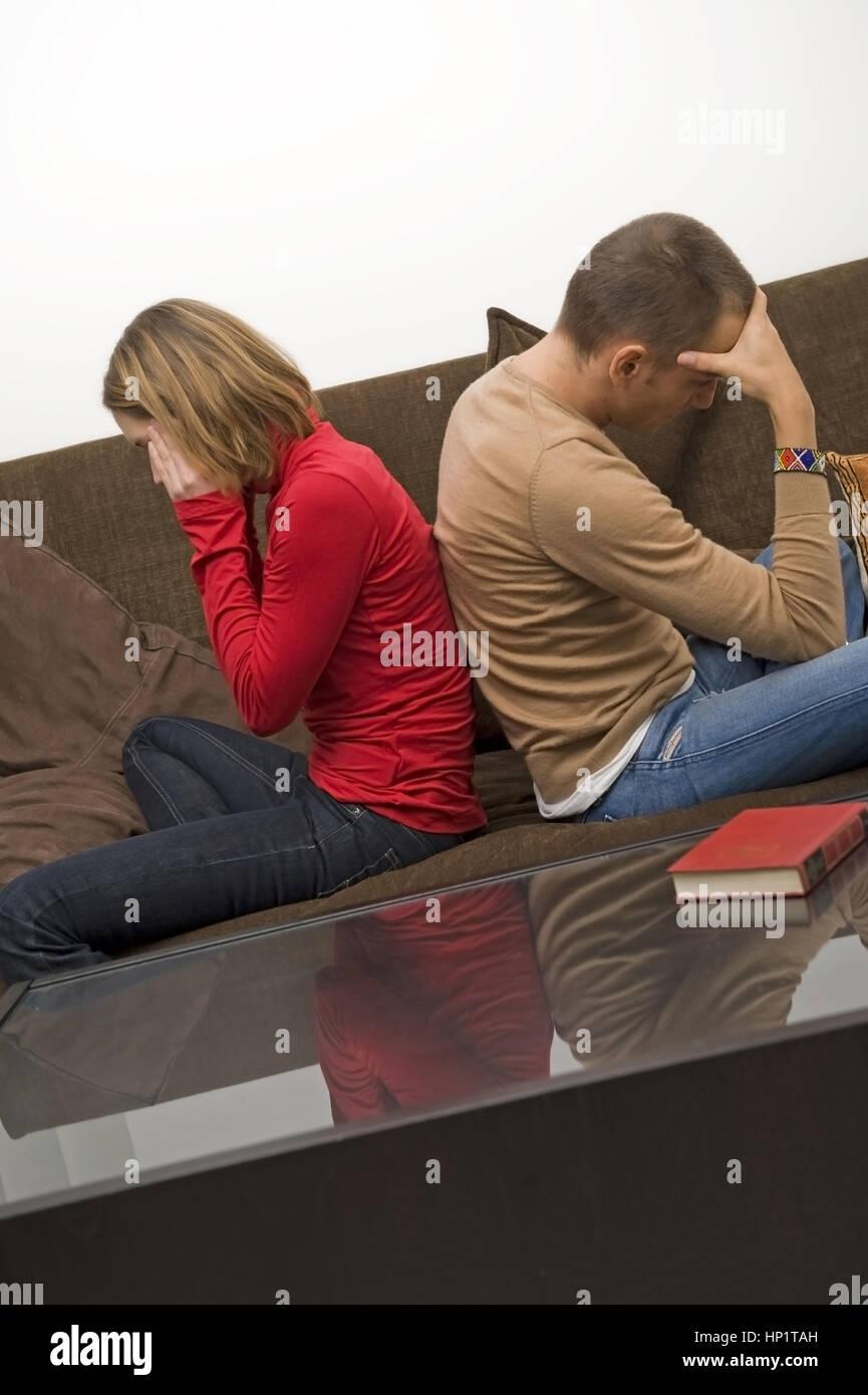 Model release , Symbolbild Beziehungsprobleme, Frau und Mann sitzten Ruecken an Ruecken auf einer Couch - symbolic for relationship problems Stock Photo