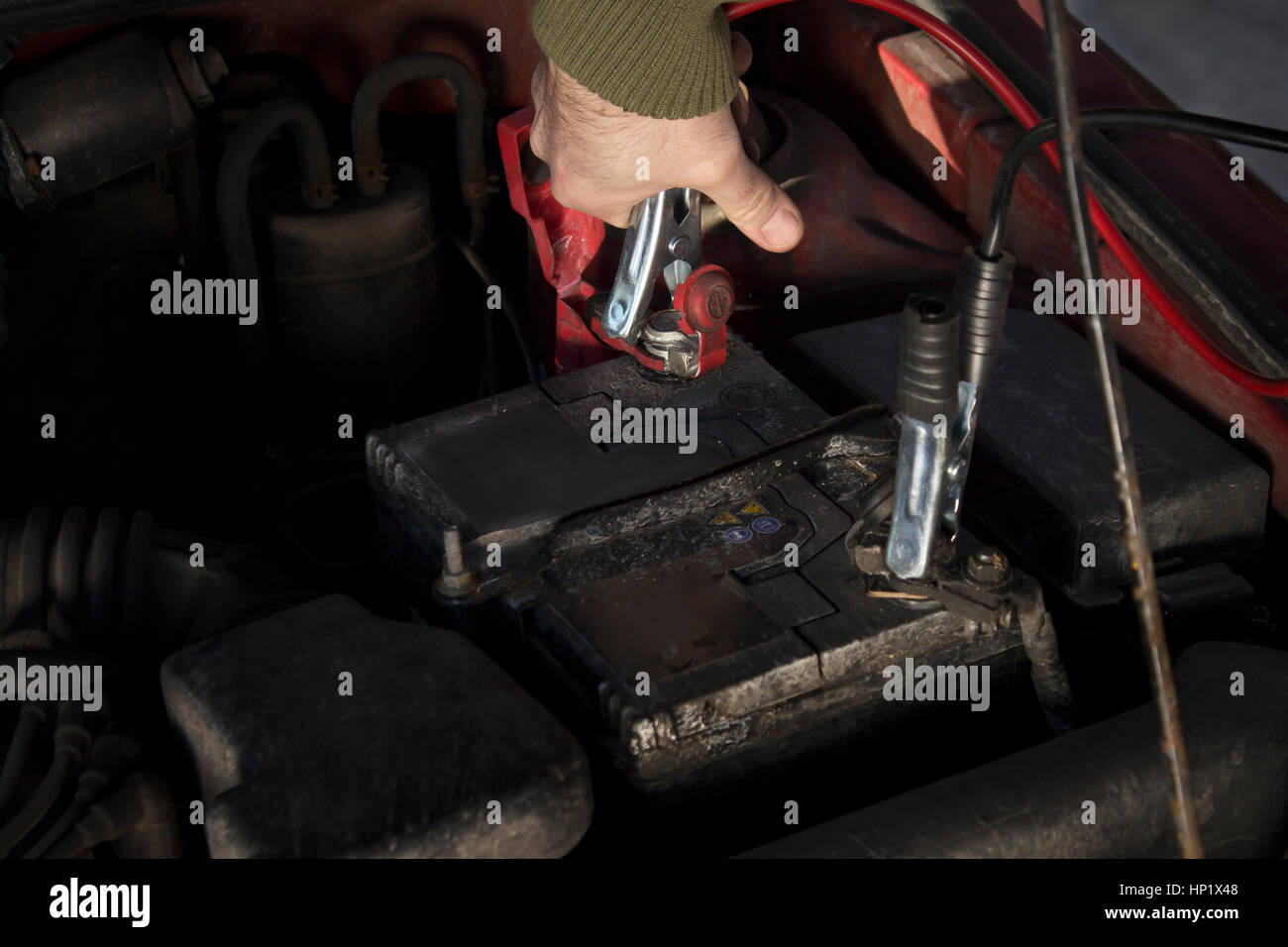 Mechanic jumper cables connected to a discharged battery. Firing the car in the winter by the jumper cables. - Stock Image