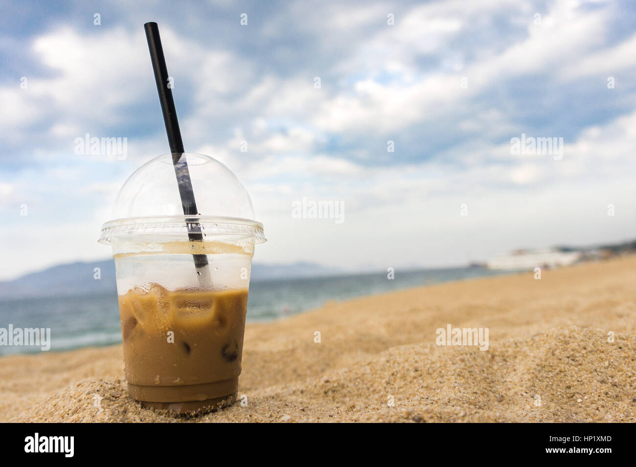 glass with black straw iced coffee is in the sand on the seashore. - Stock Image