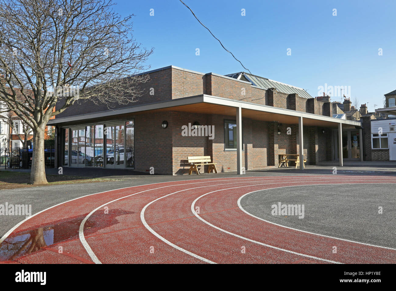A modern extension to a traditional Victorian London school building, UK. Shows all-weather running track in foreground - Stock Image