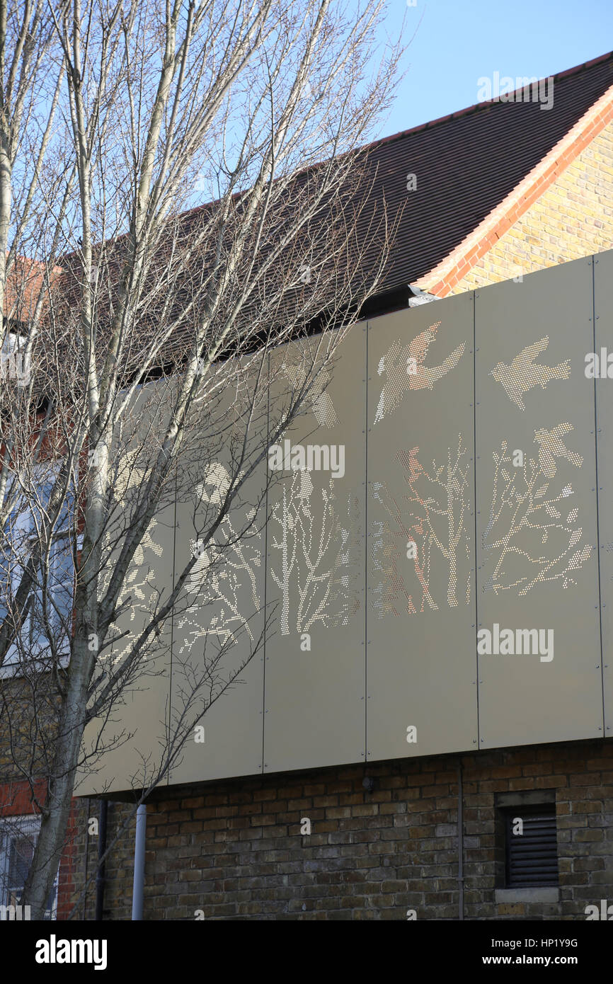 Perforated steel panels form a decorative barrier on a refurbished Victorian London school building - Stock Image