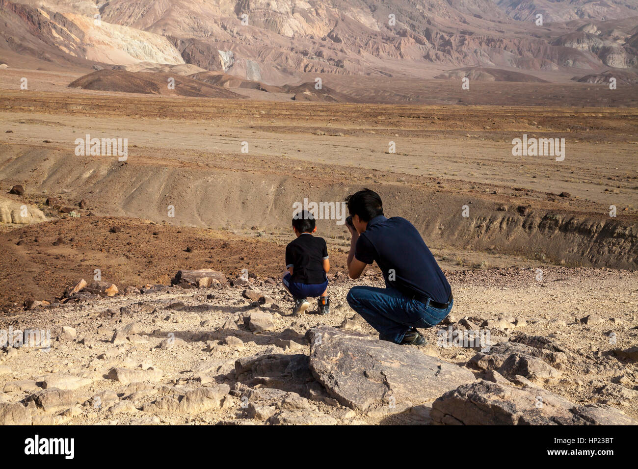 Father taking photos of son in Death Valley, California, USA - Stock Image