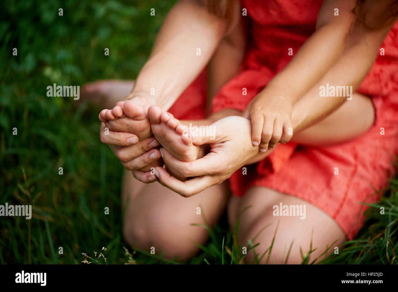 Mother holding a child, see the hands of mothers and baby feet. The feeling of care and motherhood. - Stock Image
