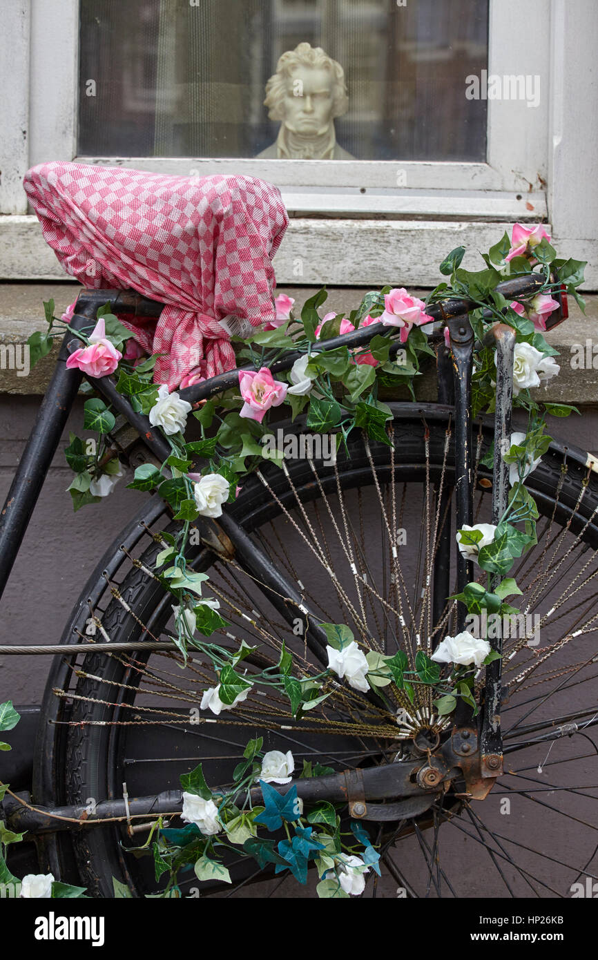 Close up of a tandem bicycle decorated with flowers, Amsterdam, Netherlands - Stock Image