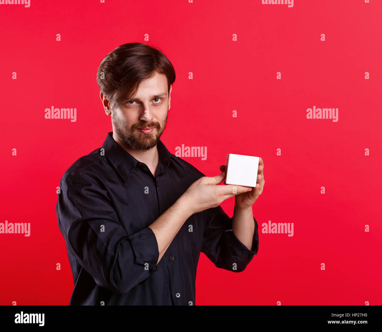 Man holding an empty cube. Advertising Space. Attractive man shows space for copy. Demonstration. - Stock Image