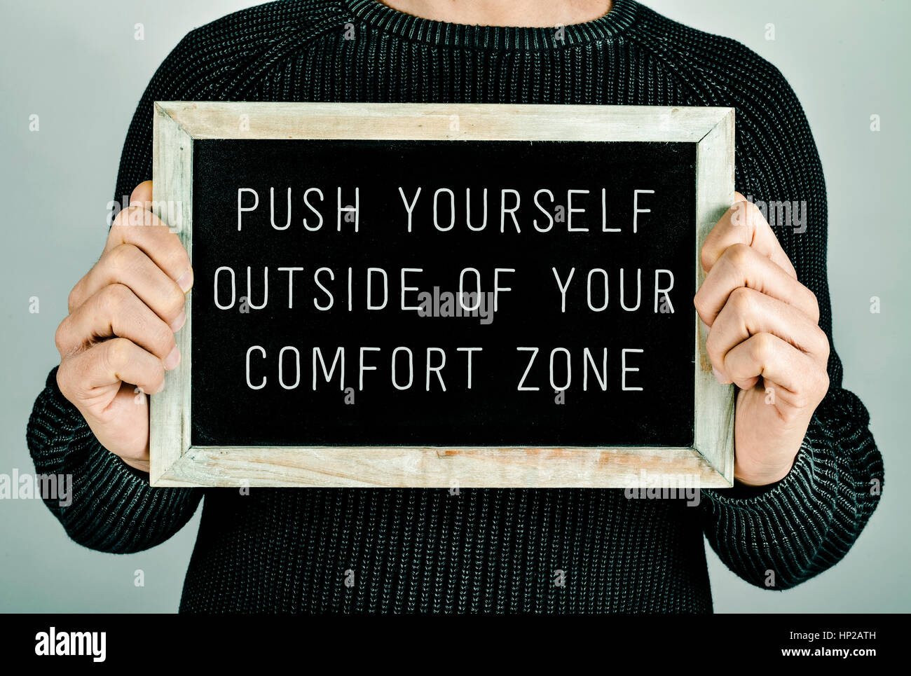 closeup of a young caucasian man holding a chalkboard in front of him with the text push yourself outside of your comfort zone written in it Stock Photo