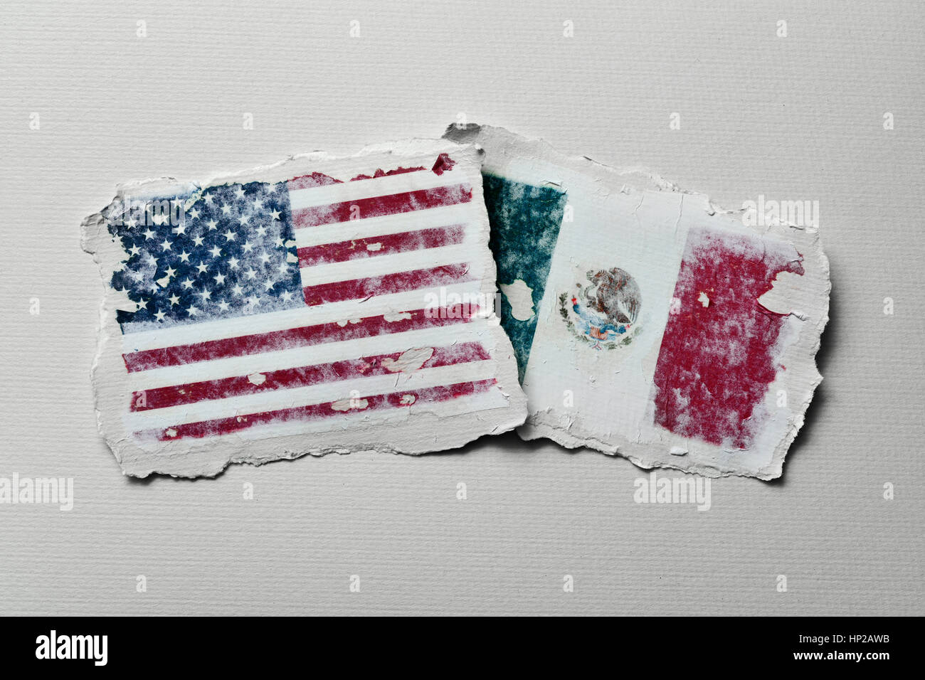 the flag of United States and the flag of Mexico in two aged pieces of paper on an off-white background - Stock Image
