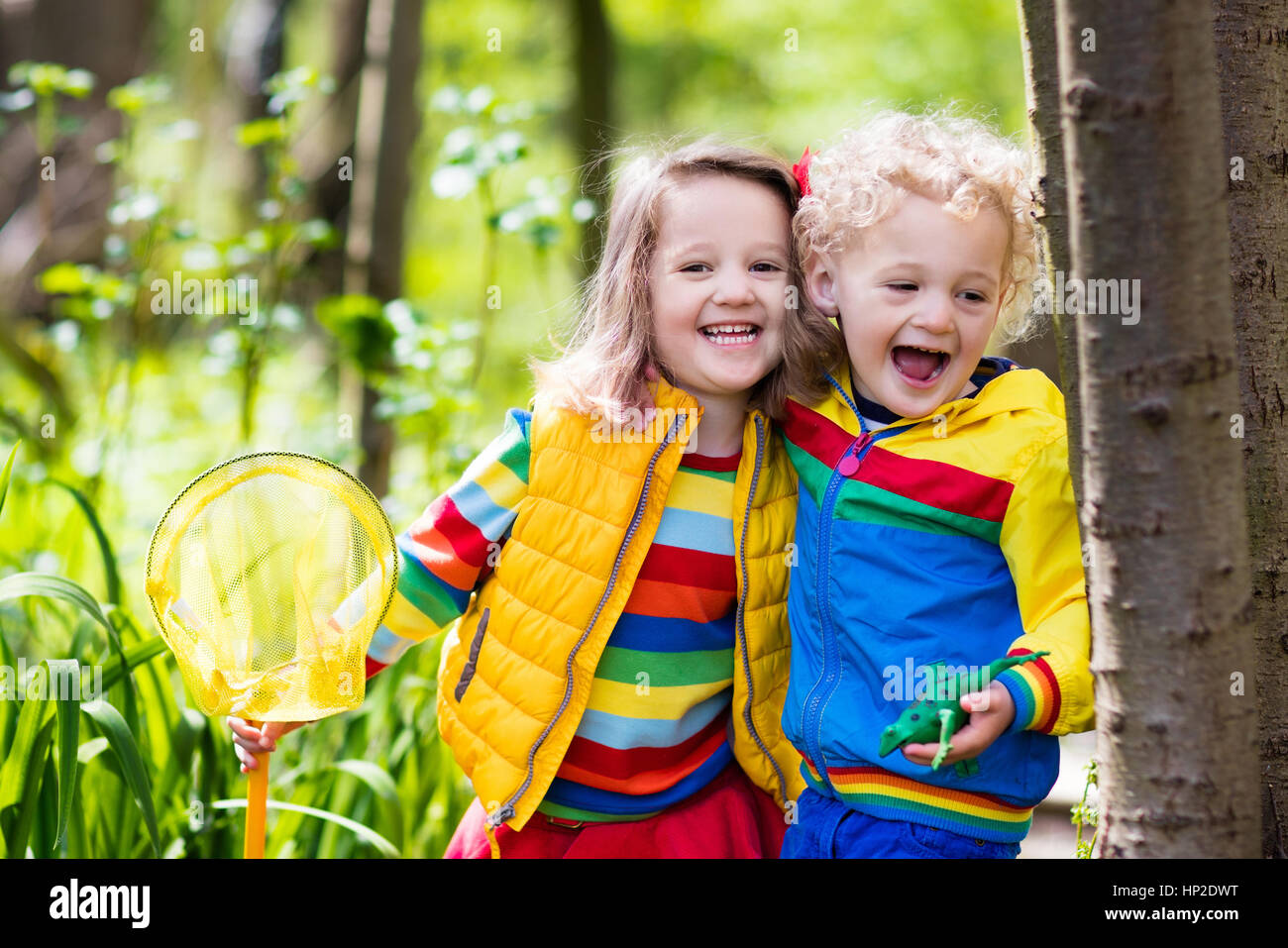 Children playing outdoors. Preschool kids catching frog with net. Boy and girl fishing in forest river. Adventure - Stock Image