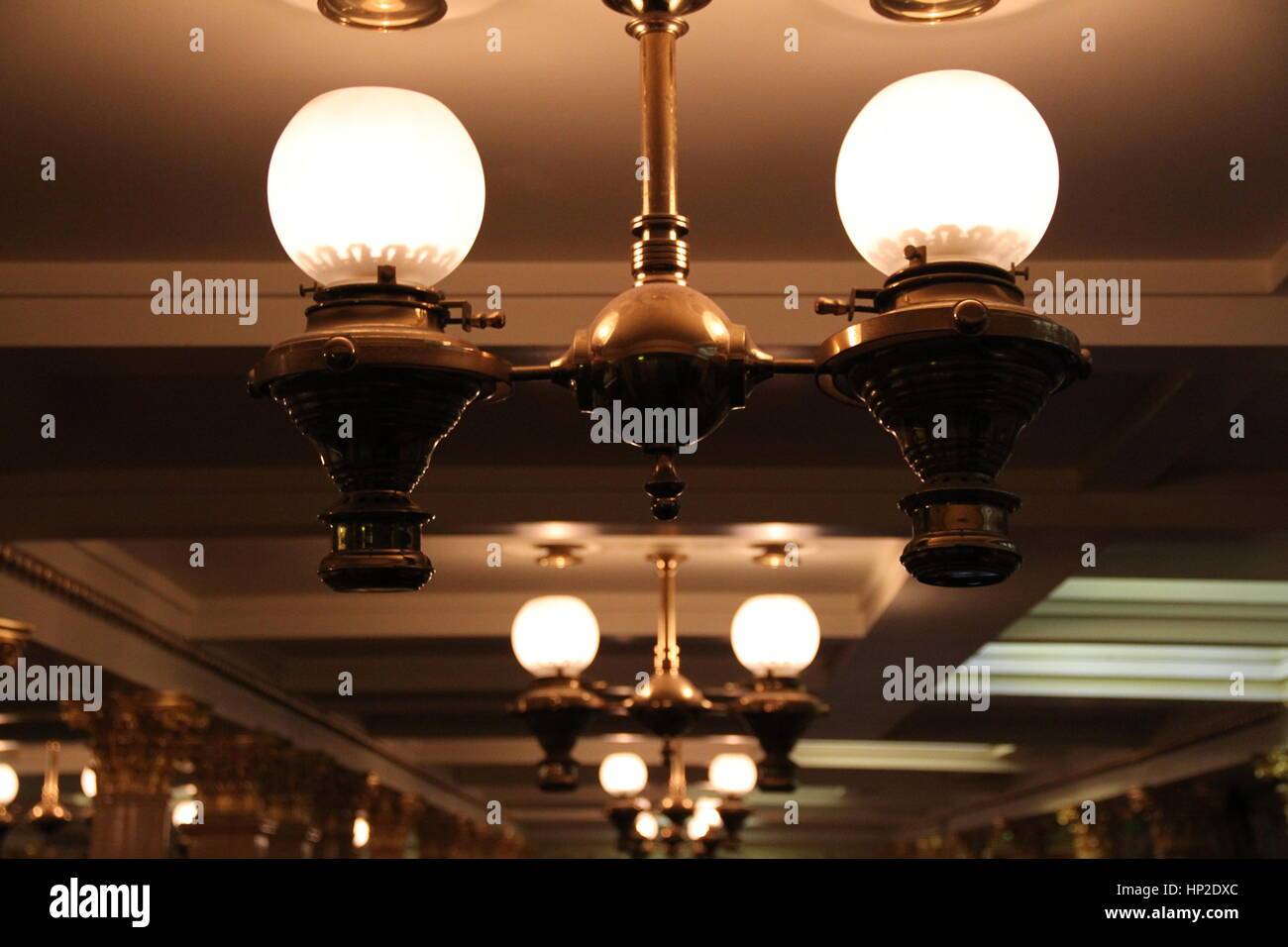 Lamps hang from the ceiling in the dining saloon of Brunel's passenger steamship SS Great Britain, Bristol. - Stock Image