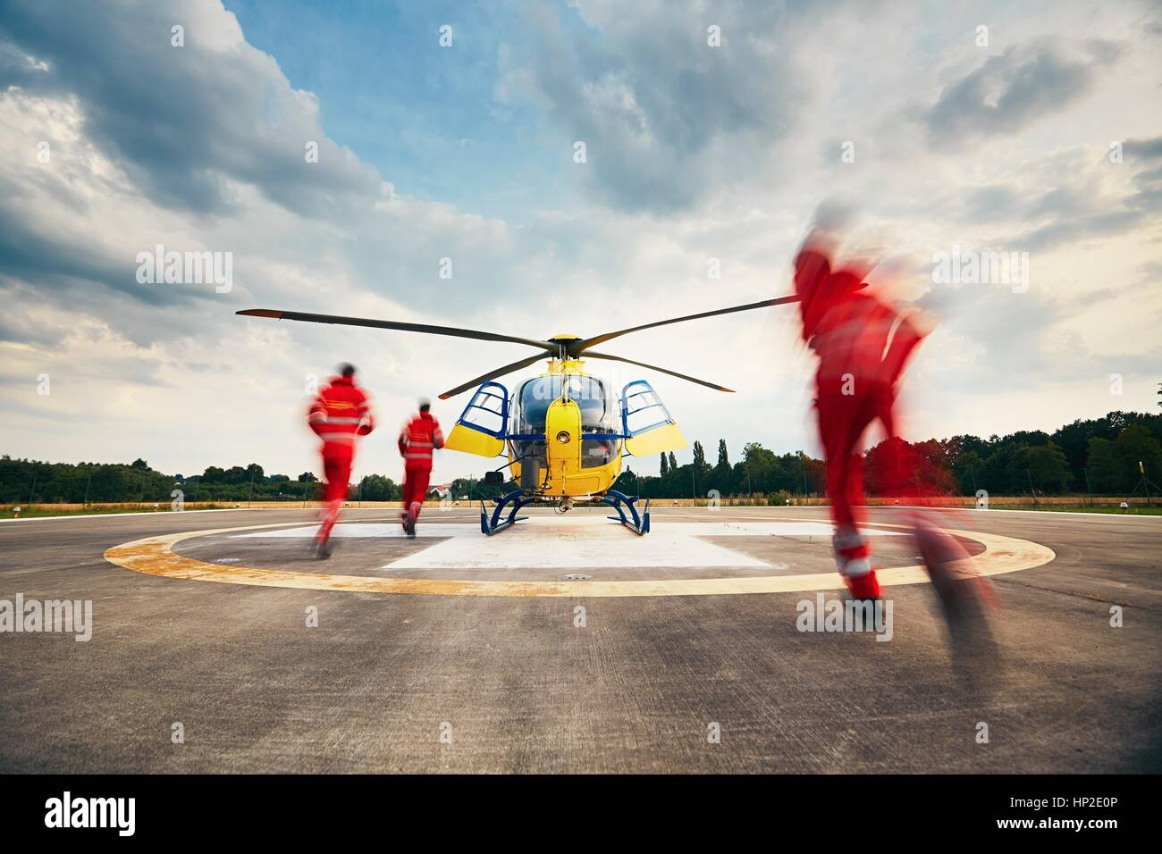 Alarm for the air rescue service. Team of rescuers (paramedic, doctor and pilot) running to the helicopter on the - Stock Image