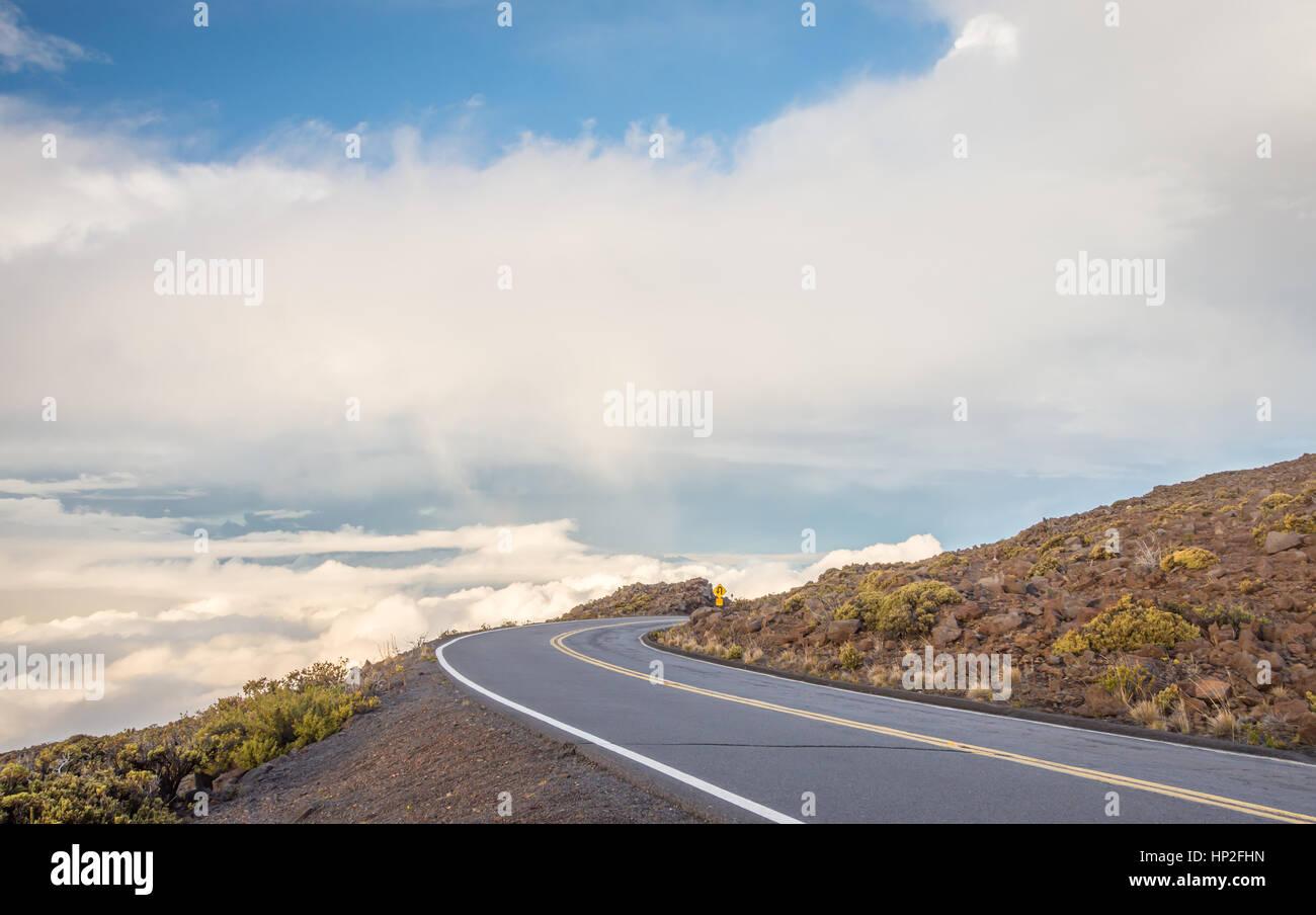 A winding mountain road high above the clouds, on the way to Haleakala on Maui, Hawaii. - Stock Image