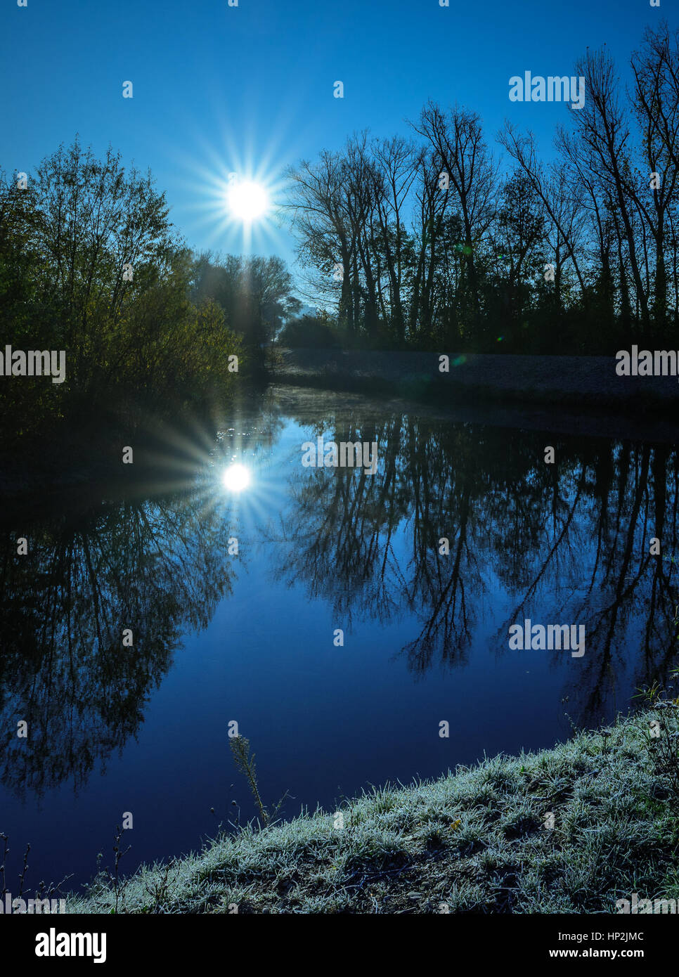 Blue clear cold November morning sunrise at a river with water reflections of sun,sunbeams and tress, hoar frost, Stock Photo