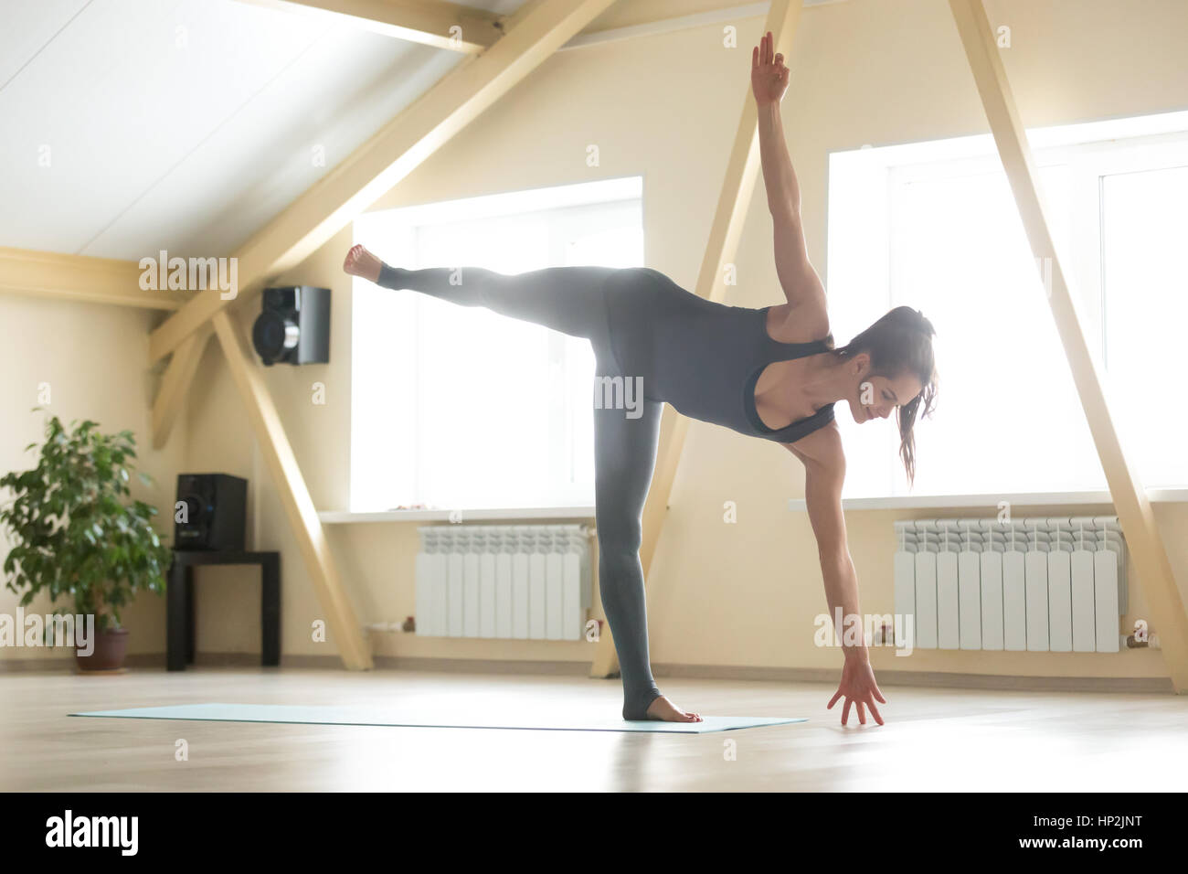 Young attractive woman standing in Ardha Chandrasana pose, home  - Stock Image