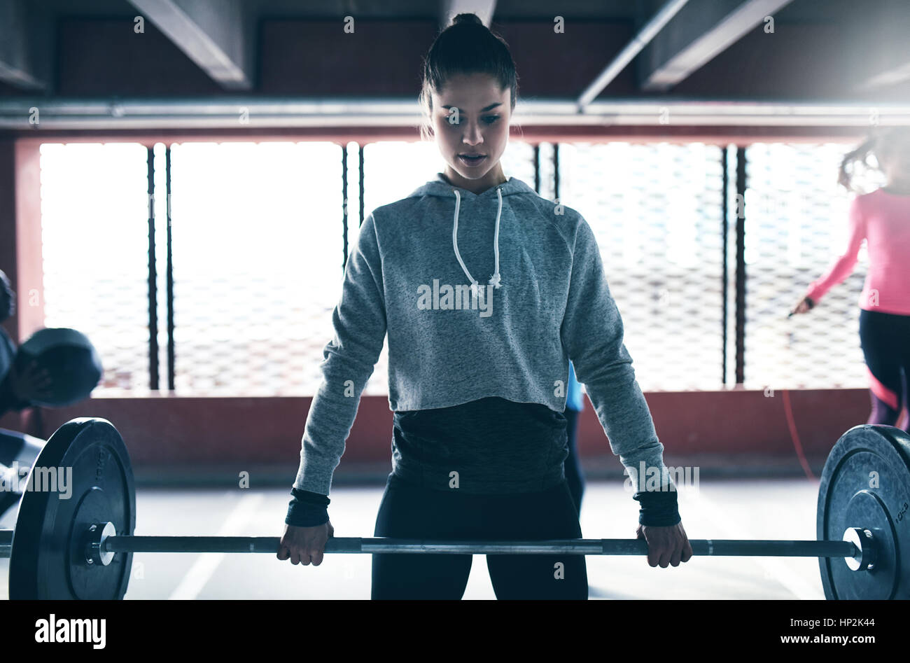 Shot of young pretty woman in sportswear training in gym and lifting barbell against barred window. - Stock Image