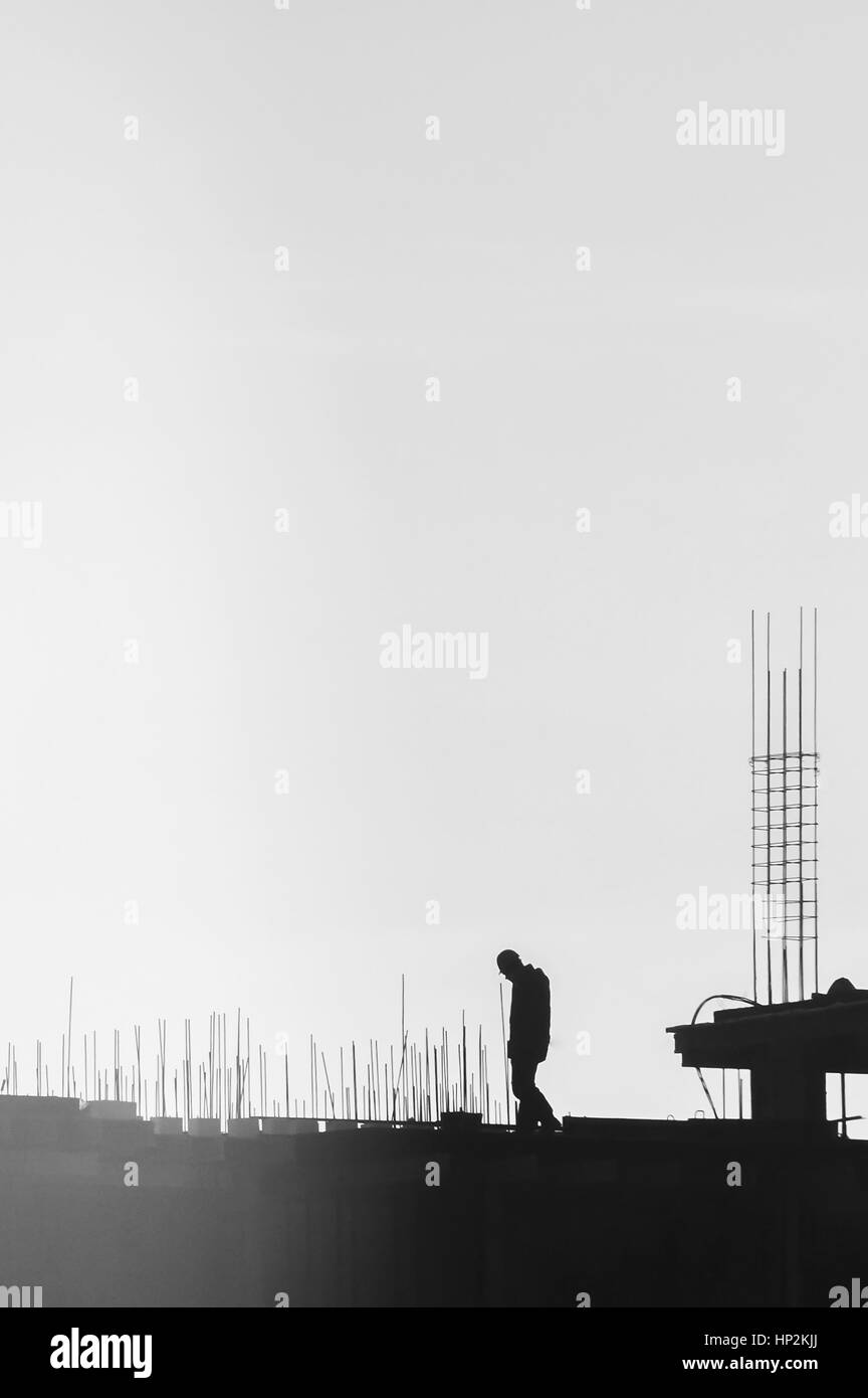 builders working on the construction site, erecting and concrete reinforcement, workflow construction, silhouette - Stock Image