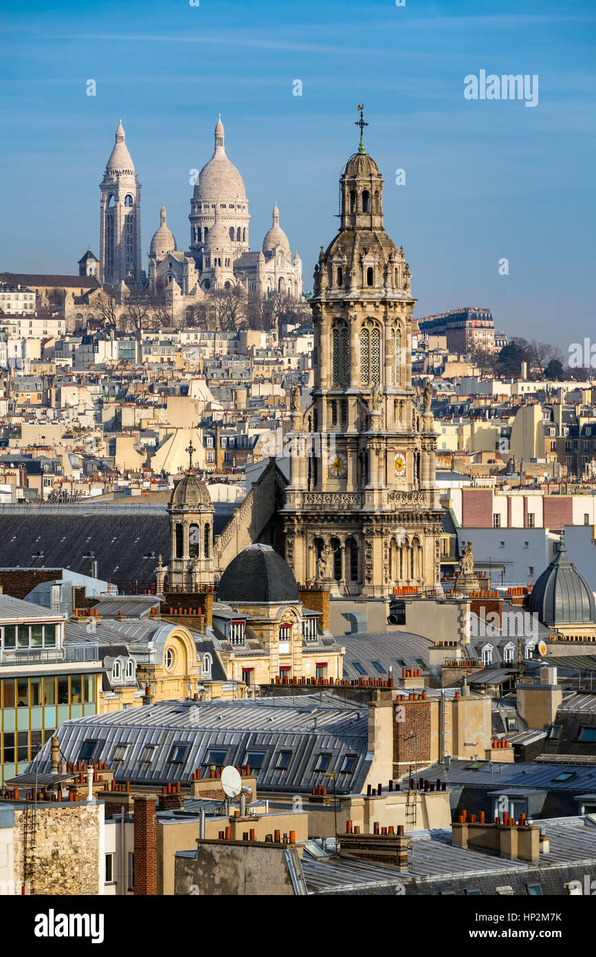 Rooftops of Paris with the Sacre Coeur Basilica in Montmartre and Trinity Church. 18th Arrondissement, Paris, France Stock Photo
