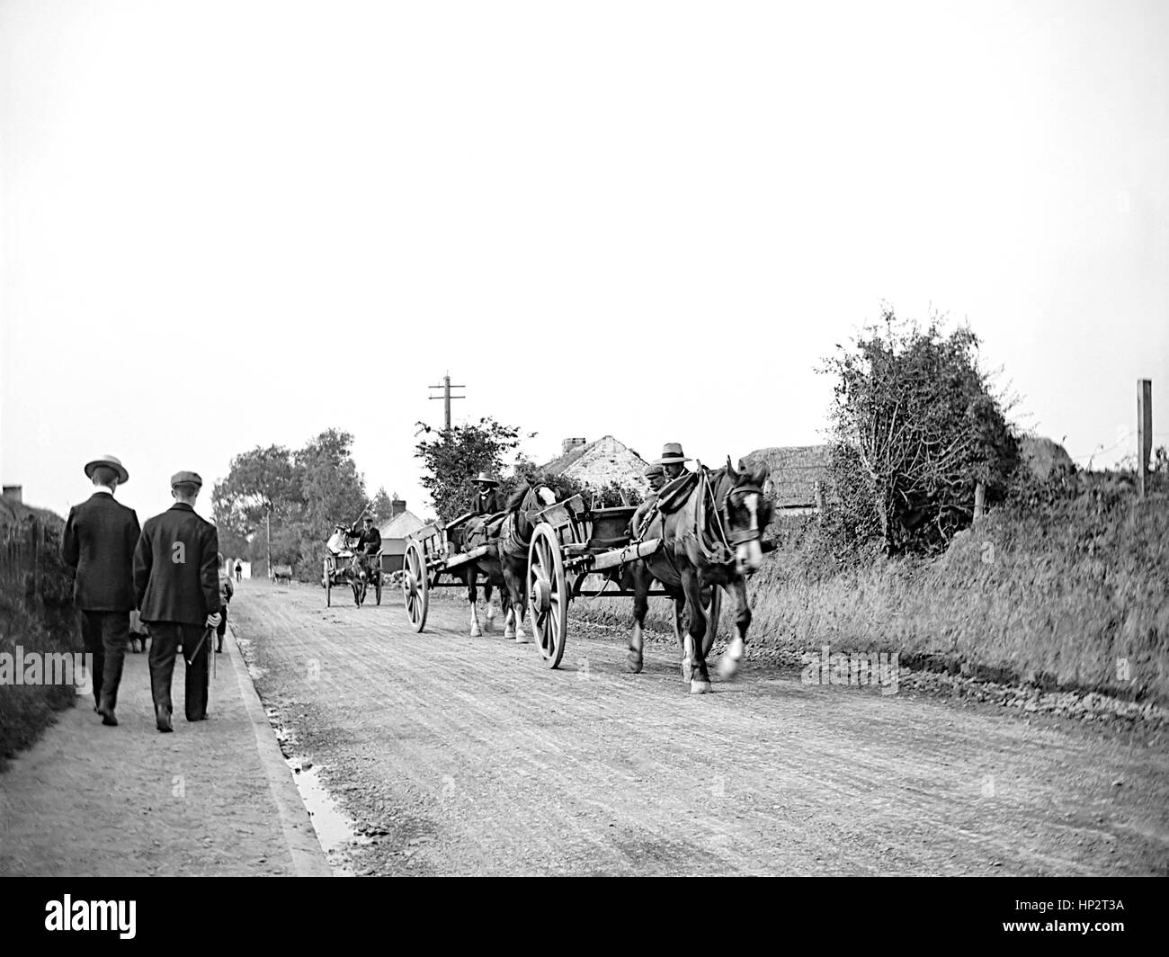 A convoy of horse drawn carts driving down a rough country lane in Kent taken in 1910. On the left is a narrow pavement - Stock Image