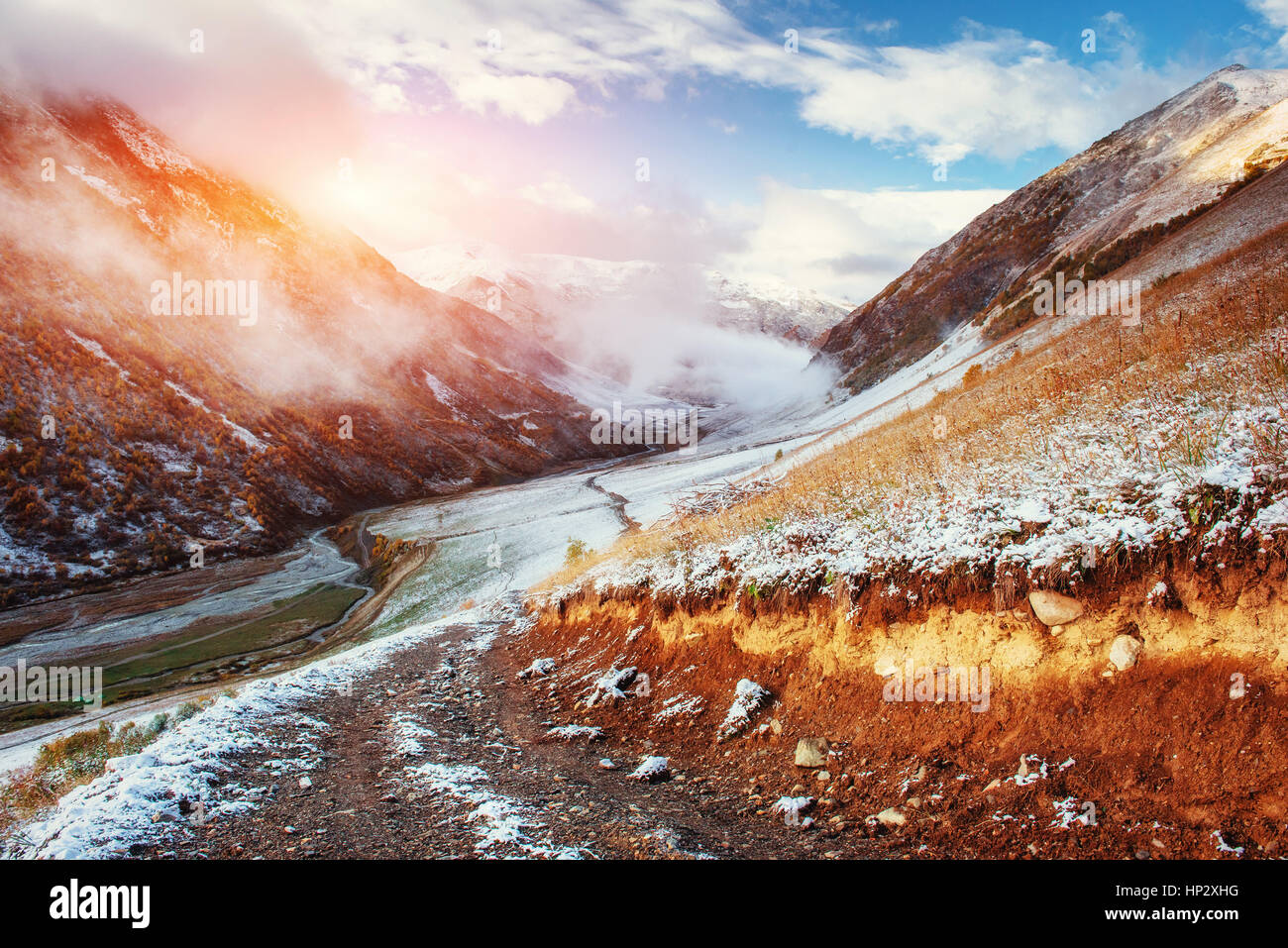 Mountain landscape of snow-capped mountains in the mist - Stock Image