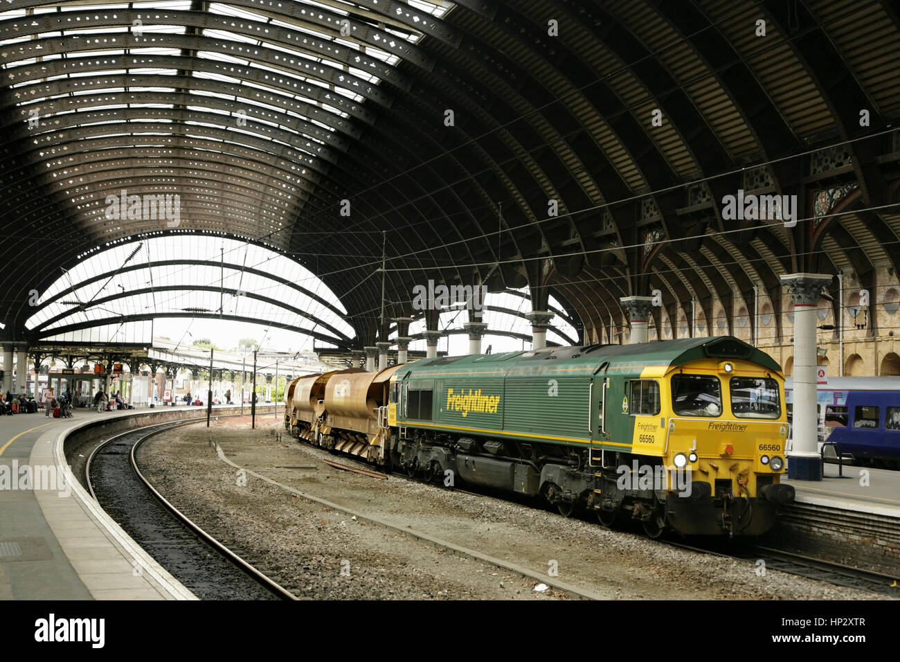 Freightliner Class 66 diesel loco with train of Network Rail ballast wagons at York station, UK - Stock Image
