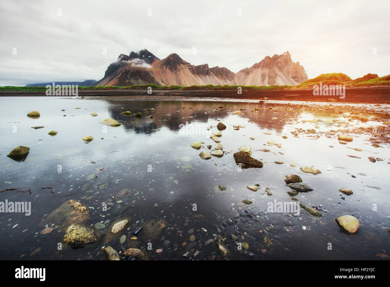 Amazing mountains reflected in the water at sunset. Stoksnes, Ic - Stock Image