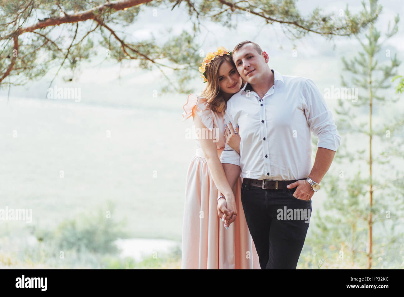 Happy young couple in a pine forest in summer - Stock Image