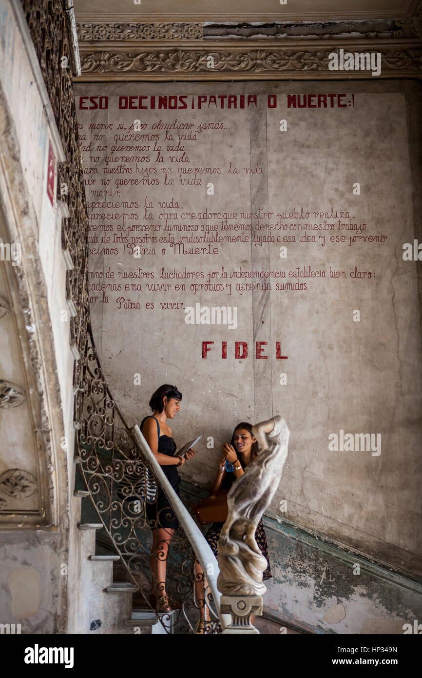 Woman, Girl, under Revolutionary, political, propaganda, message by Fidel Castro, in entrance to the Paladar La - Stock Image