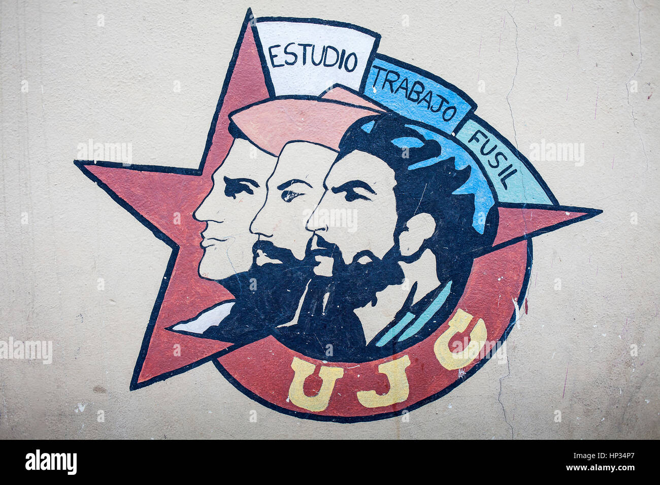Political propaganda. Emblem of UJC, Union of Young Communists, faces of Mella, Cienfuegos y Che, painted on a street - Stock Image