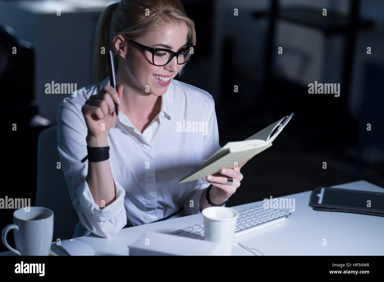 Smiling secretary enjoying her responsibilities in the office - Stock Image