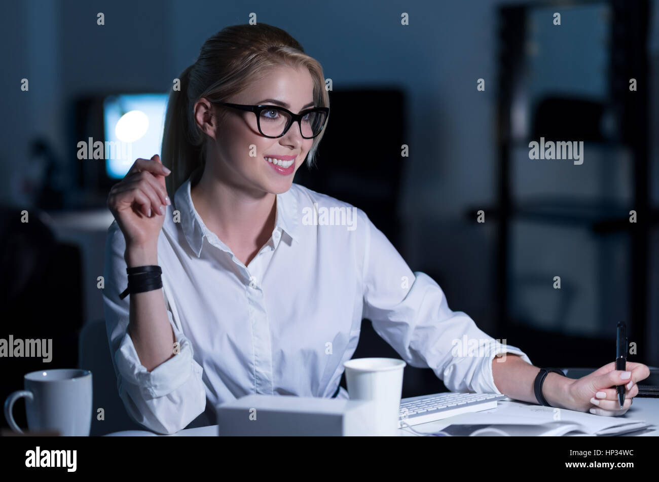 Cheerful positive secretary taking notes in the office - Stock Image