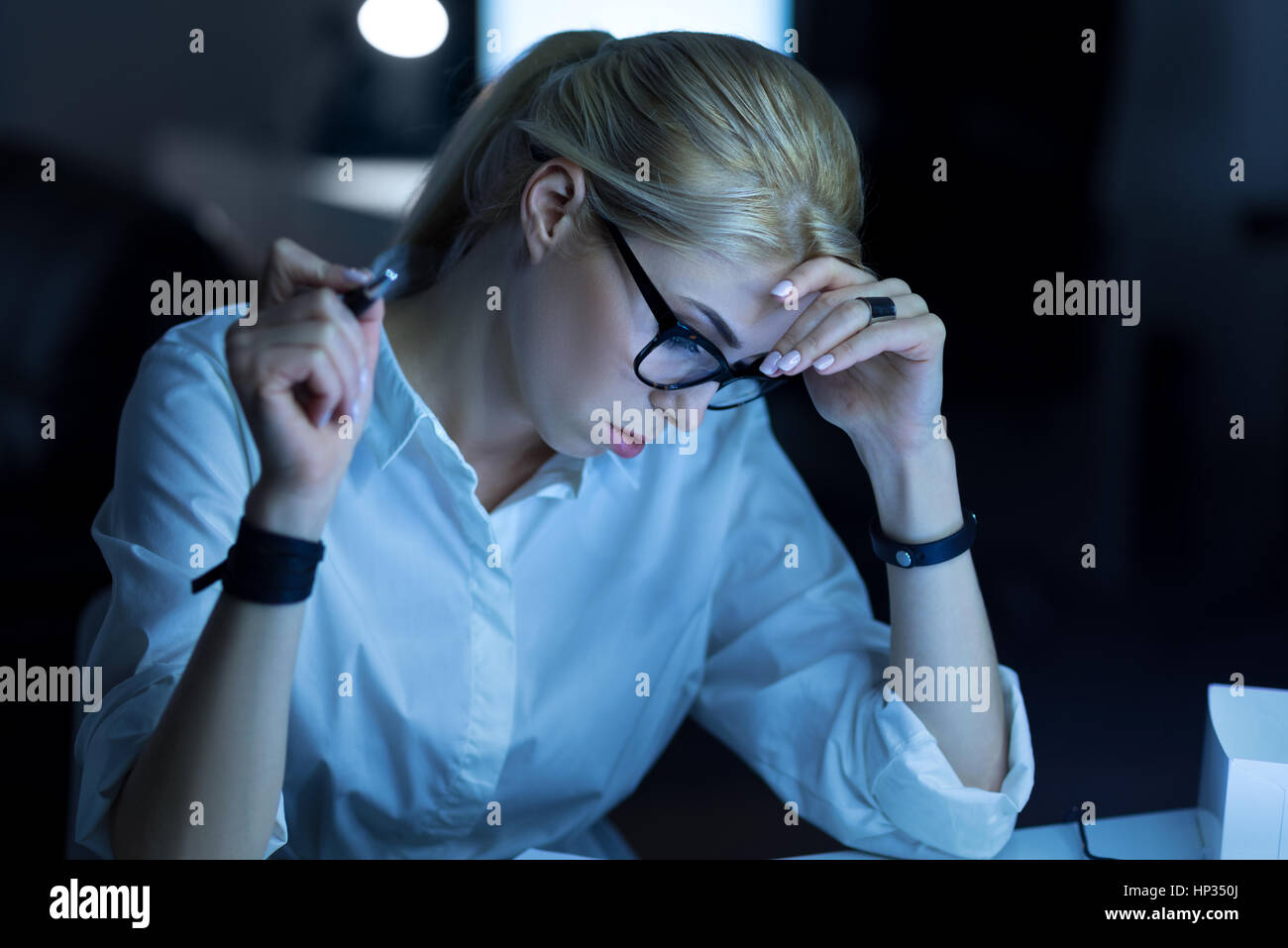 Serious young woman working with papers in the office - Stock Image