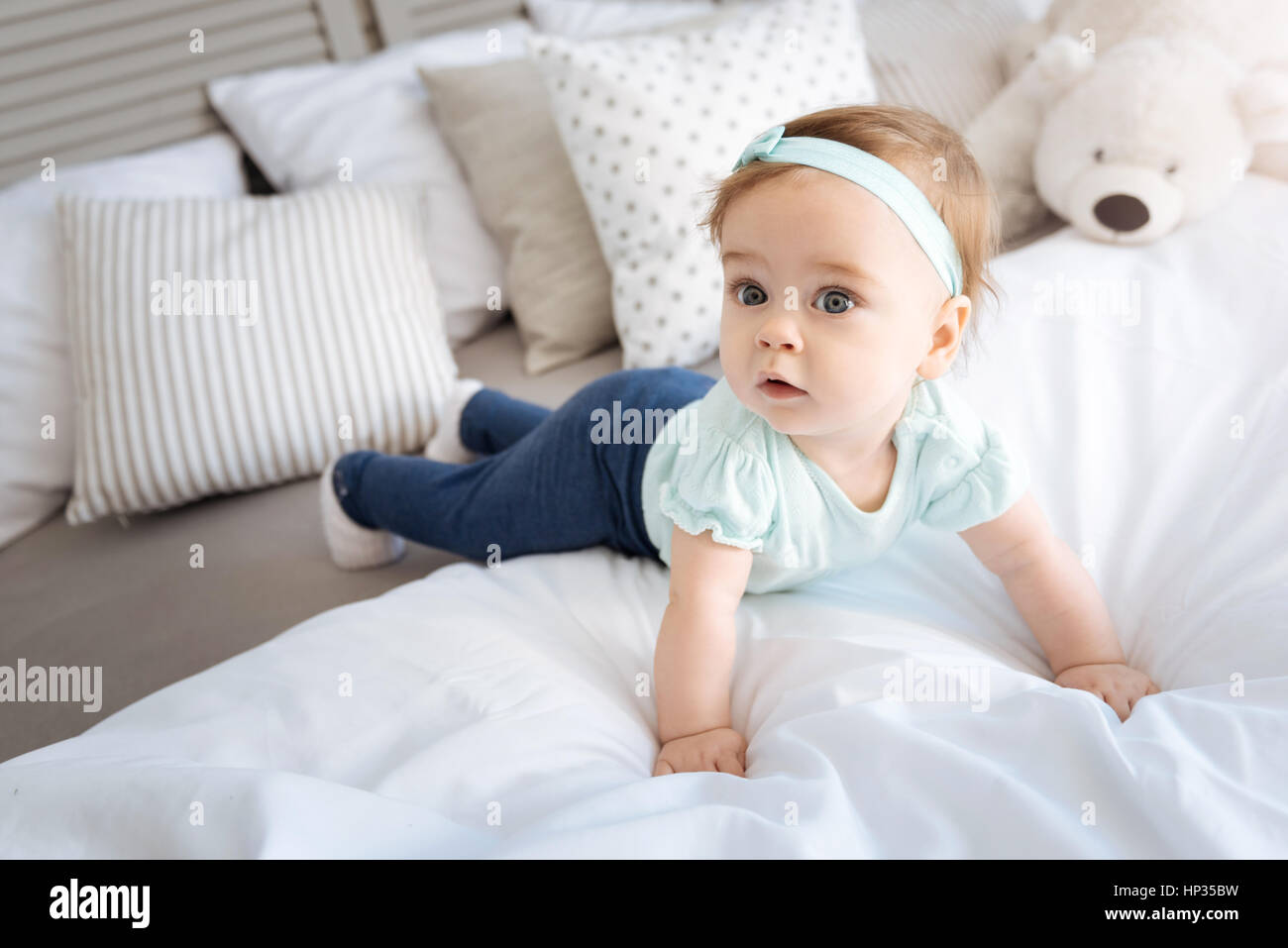 Cute surprised kid lying on the bed at home - Stock Image
