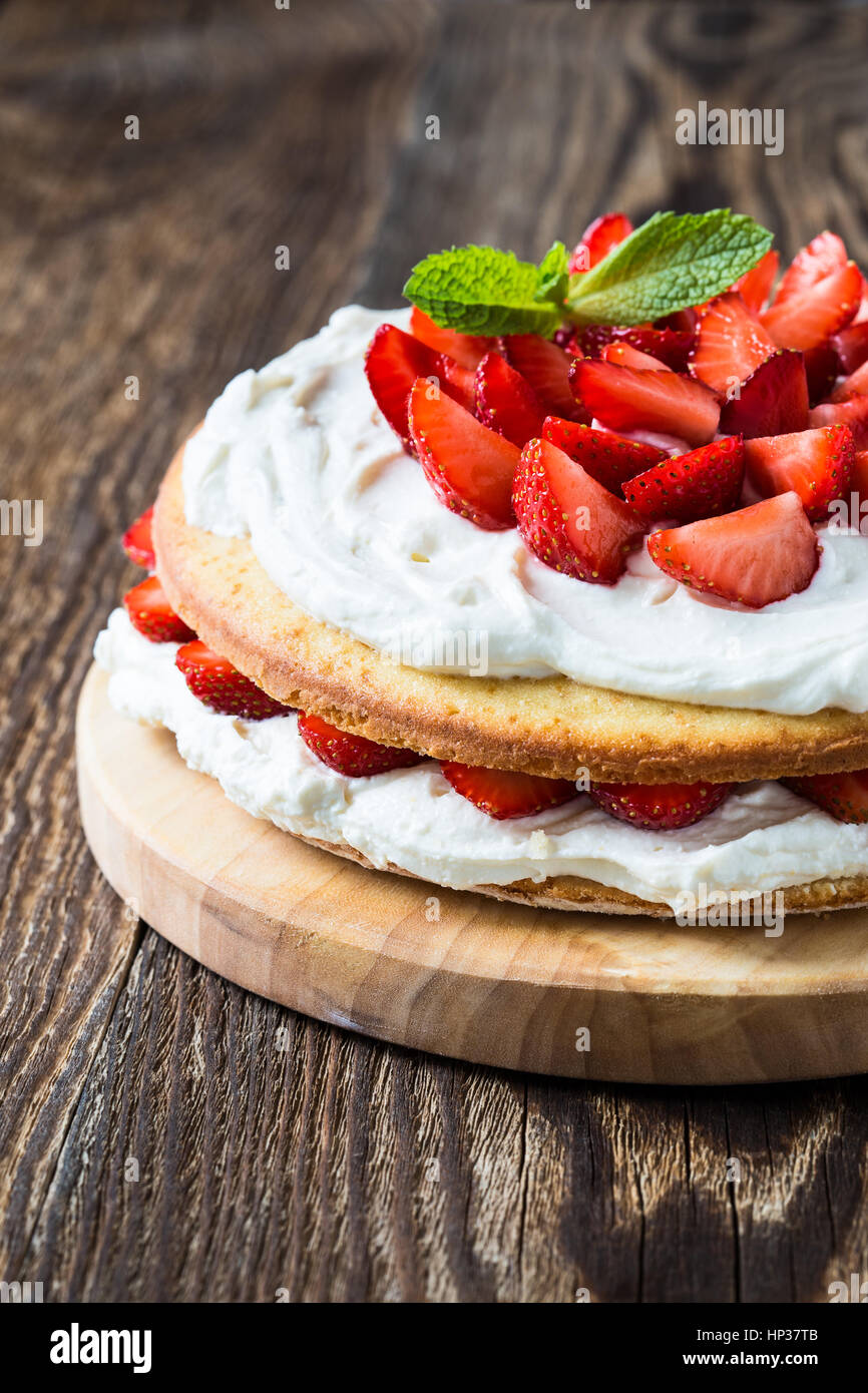 Homemade cream layer cake, fresh, colorful, and delicious dessert with juicy strawberries, and sweet whipped cream. - Stock Image